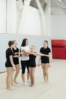 Entrenador de porristas joven explicando el elemento de baile a las niñas mientras ajusta la posición de la chica rubia