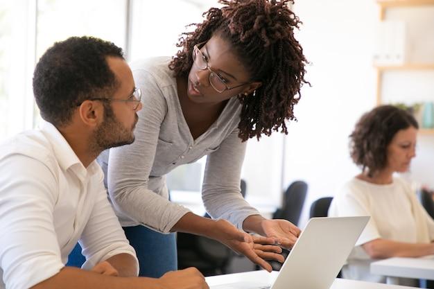 Entrenador que explica los detalles del software al nuevo empleado
