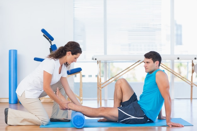 Entrenador que trabaja con el hombre en la estera del ejercicio