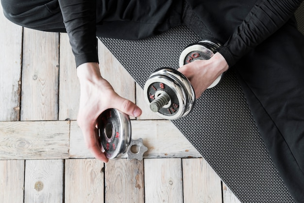 Entrenador sentado en el piso y preparando pesas