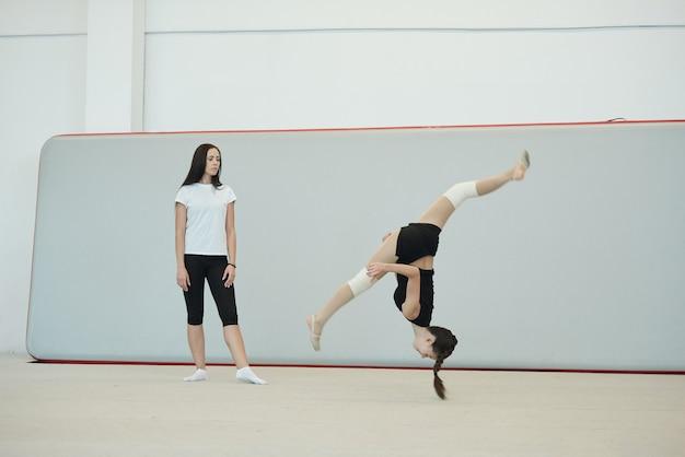 Entrenador de sexo femenino joven en calcetines de pie en el pabellón de deportes y evaluación de las habilidades de la niña porristas saltando por encima de la cabeza en el entrenamiento