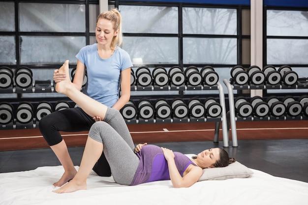 Entrenador sonriente moviendo la pierna de la mujer embarazada en el gimnasio