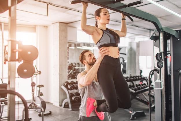 El entrenador y su alumno están en el gimnasio. él la está ayudando a detenerse.