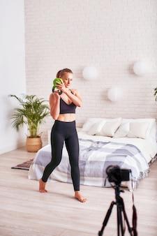 El entrenador de transmisión en línea muestra la técnica de realizar ejercicios con pesas. entrenamiento de los músculos de la mano.