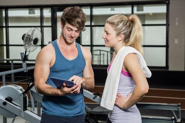 Entrenador usando una tableta digital mientras habla con una mujer