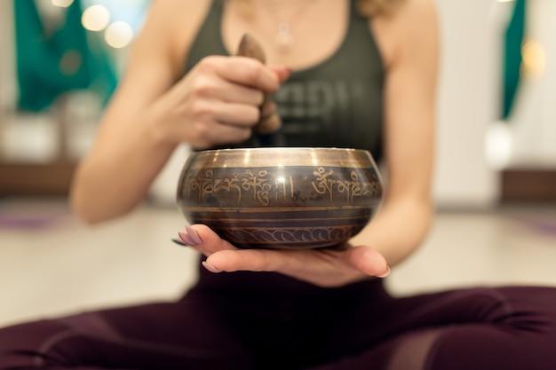 Entrenador yoga con el bowl de meditación introduce sus salas en un trance