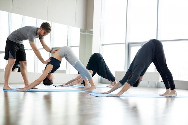 Entrenador de yoga calificado que ayuda a los estudiantes en clase