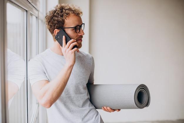 Entrenador de yoga con estera hablando por teléfono y de pie junto a la ventana