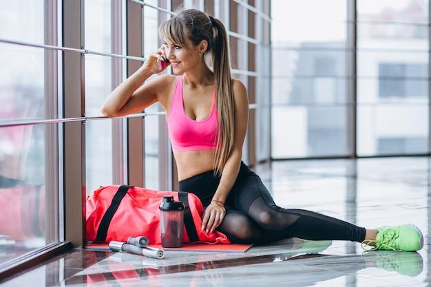 Entrenador de yoga femenino usando el teléfono