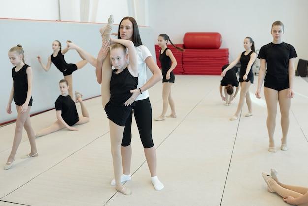 Entrenadora joven que ayuda a una chica flexible a hacer split de pie sobre una pierna mientras otras chicas realizan ejercicios de calentamiento