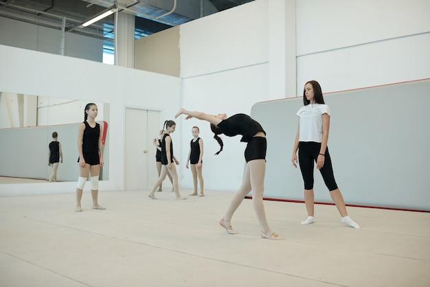 Entrenadora joven que evalúa la flexibilidad de las niñas para el equipo de porristas durante el entrenamiento en la escuela