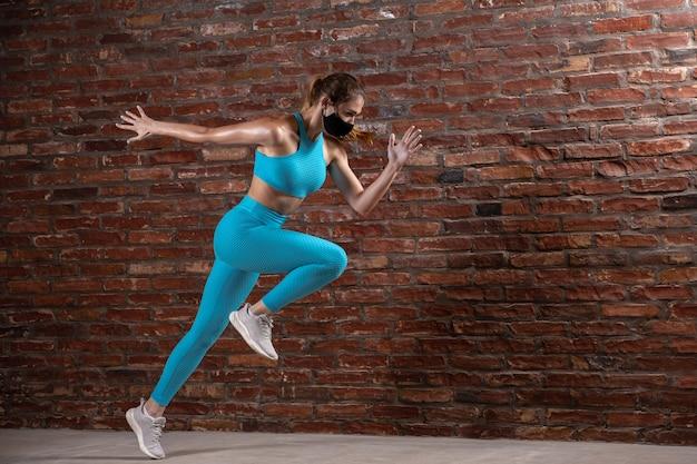 Entrenamiento de la atleta femenina profesional en la pared de ladrillo que lleva la mascarilla.