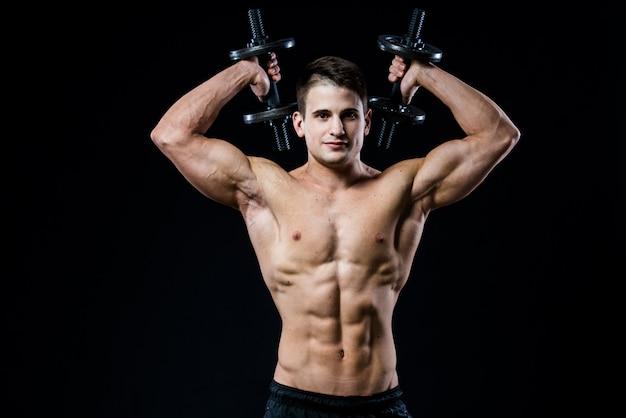 Entrenamiento atlético del hombre del poder hermoso que bombea los músculos con pesas en un gimnasio. barbells detrás de la cabeza. cuerpo musculoso fitness aislado.