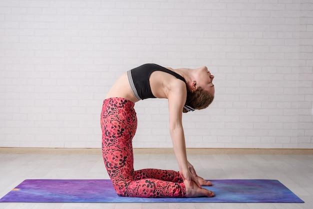 Entrenamiento de auto yoga en casa. joven hermosa chica practica yoga en casa.