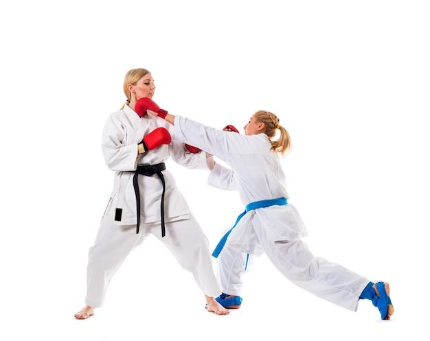 Entrenamiento de boxeo de dos mujeres jóvenes con kimonos blancos y guantes de boxeo