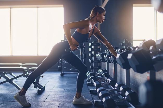 Entrenamiento de chica deportiva con mancuerna en el gimnasio