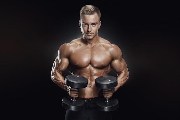 Entrenamiento de chico guapo atlético con pesas