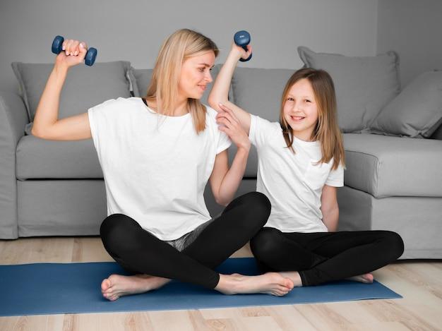 Entrenamiento deportivo de madre y niña con pesas