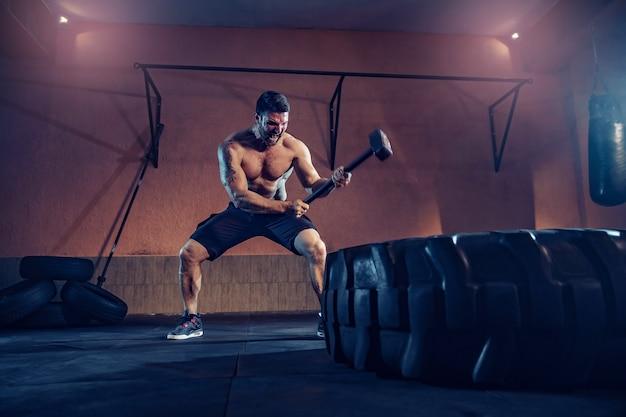 Entrenamiento deportivo para la resistencia, el hombre golpea el martillo. entrenamiento de concepto.