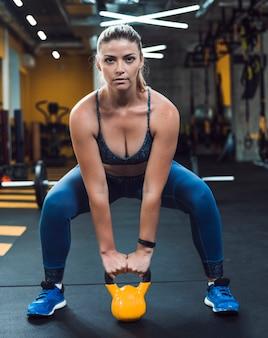 Entrenamiento ding de la mujer joven hermosa con la bola de la caldera en club de fitness