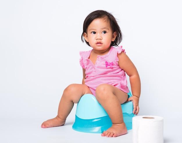 Entrenamiento educativo de niña pequeña para sentarse en el orinal