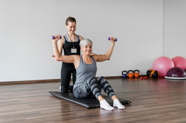 Entrenamiento con ejercicio de brazo de entrenador personal con mancuernas