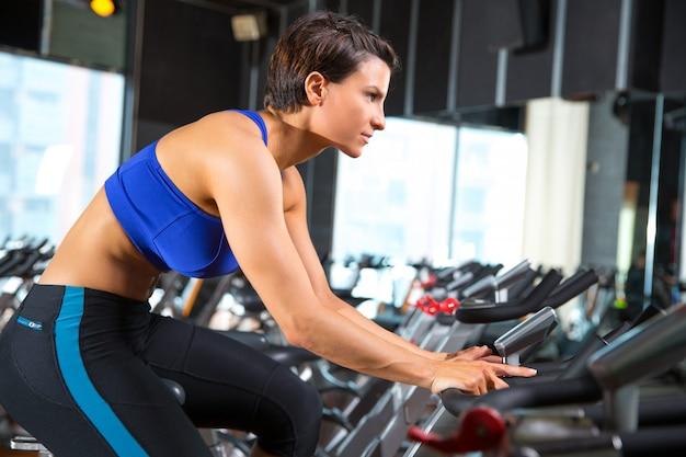 Entrenamiento de ejercicios aeróbicos spinning mujer en el gimnasio