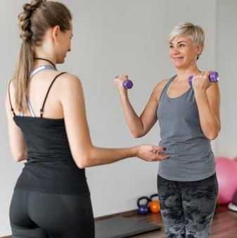 Entrenamiento con entrenador personal usando mancuernas violetas