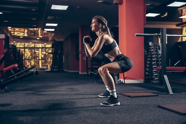 Entrenamiento de entrenamiento deportivo joven hermosa en gimnasio