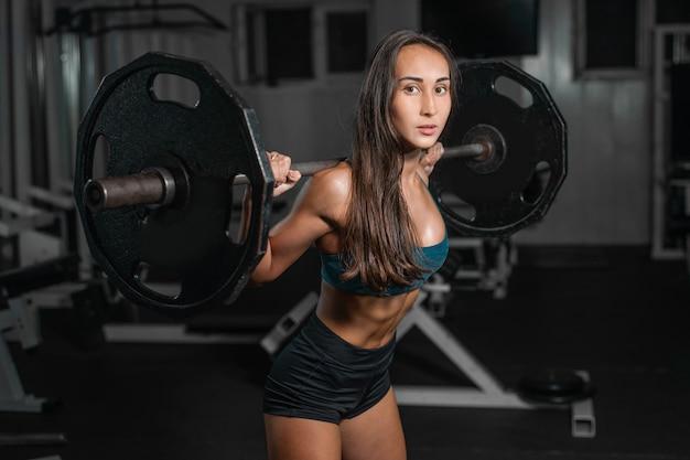 Entrenamiento femenino con barra, bombeo de piernas