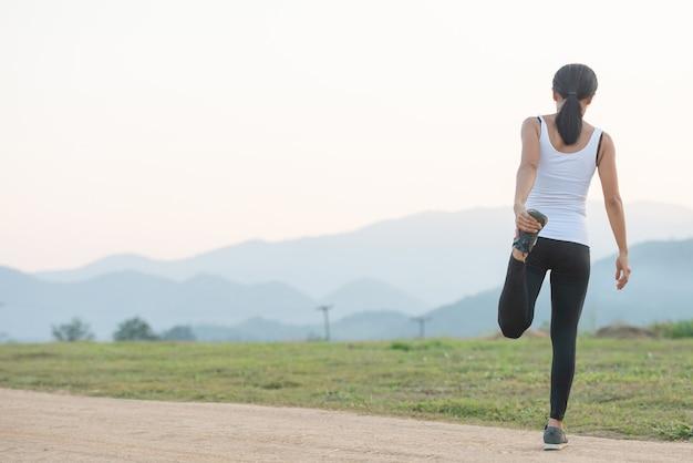 Entrenamiento femenino joven antes de la sesión de entrenamiento físico en el parque.