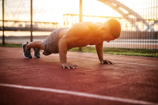 Entrenamiento físico al aire libre. ejercicios de trabajo de hombre guapo temprano en la mañana con amanecer. hombre musculoso entrenando afuera. mañana soleada de fitness.