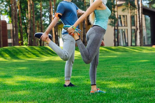 Entrenamiento físico. bonitos jóvenes de pie juntos sobre la hierba mientras hacen un ejercicio de estiramiento