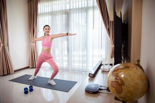 Entrenamiento físico de la mujer asiática en casa. está aprendiendo nuevos ejercicios viendo tutoriales de ejercicios en línea sobre ella en casa.