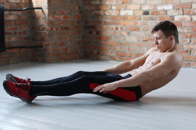 Entrenamiento de fitness hombre. hombre sin camisa haciendo estiramientos en casa