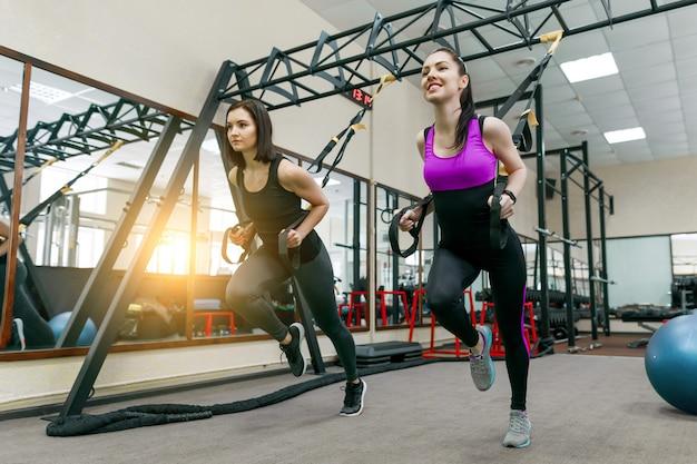 Entrenamiento grupal con bucles en el gimnasio, dos mujeres de fitness haciendo cross fit