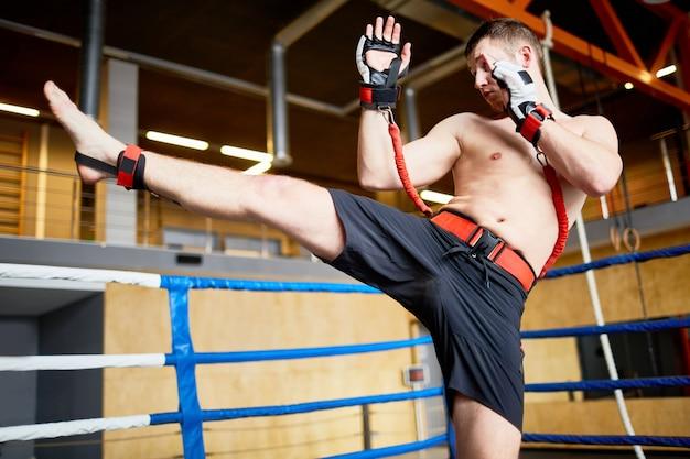 Entrenamiento de kickboxer con cinturones de resistencia