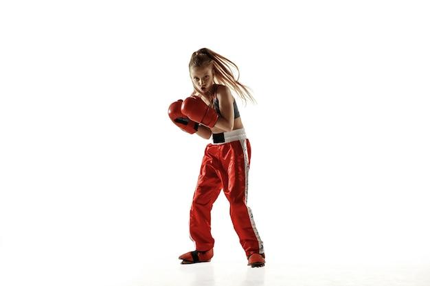 Entrenamiento de luchador de kickboxing femenino joven aislado en la pared blanca. chica rubia caucásica en ropa deportiva roja practicando artes marciales. concepto de deporte, estilo de vida saludable, movimiento, acción, juventud.
