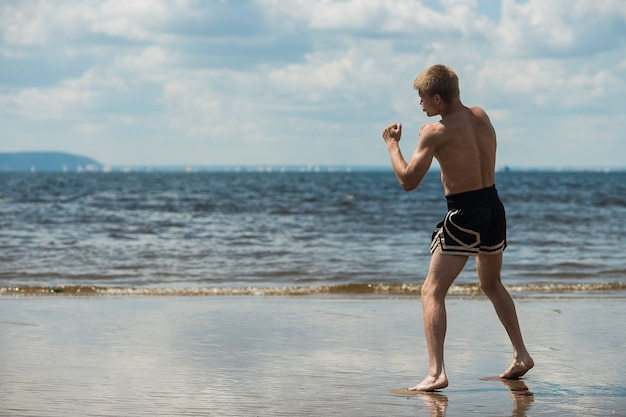 Entrenamiento de luchador masculino musculoso, boxer entrena al aire libre