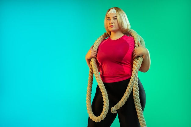 Entrenamiento del modelo femenino caucásico joven del tamaño extra grande en fondo verde degradado en luz de neón. haciendo ejercicios de entrenamiento con las cuerdas. concepto de deporte, estilo de vida saludable, cuerpo positivo, igualdad.