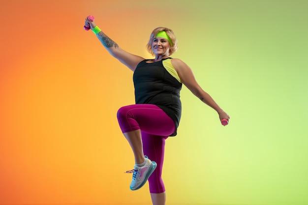 Entrenamiento del modelo femenino caucásico joven del tamaño extra grande en la pared anaranjada del gradiente en luz de neón.