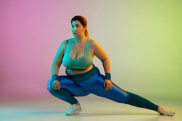 Entrenamiento del modelo femenino caucásico joven del tamaño extra grande en la pared verde púrpura del gradiente en neón. haciendo ejercicios de estiramiento. concepto de deporte, estilo de vida saludable, cuerpo positivo, igualdad.