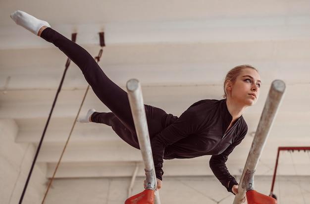 Entrenamiento de mujer de ángulo bajo para campeonato de gimnasia