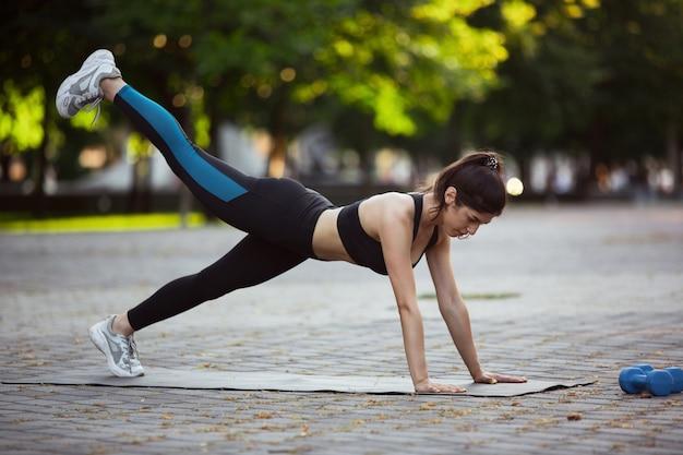 Entrenamiento de la mujer atleta en la calle de la ciudad, día de verano