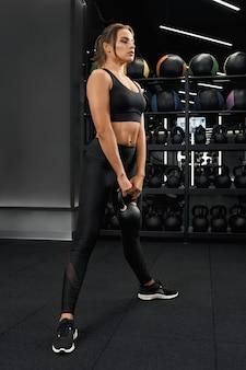 Entrenamiento de mujer deportiva con pesas rusas en el gimnasio moderno