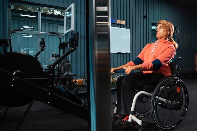 Entrenamiento de mujer discapacitada en el gimnasio del centro de rehabilitación