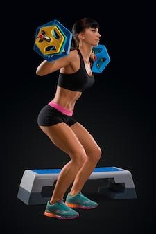 Entrenamiento de mujer fitness con barra en el gimnasio