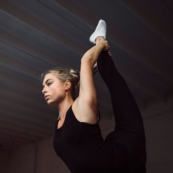 Entrenamiento de mujer joven de ángulo bajo para juegos olímpicos de gimnasia