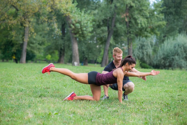 Entrenamiento de mujer joven con su entrenador personal en el parque