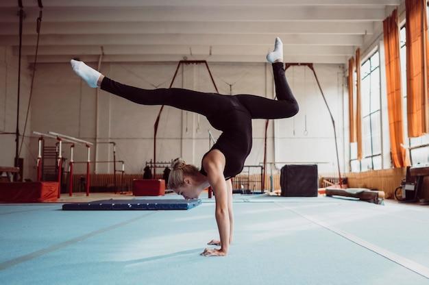Entrenamiento de mujer lateral para el campeonato de gimnasia